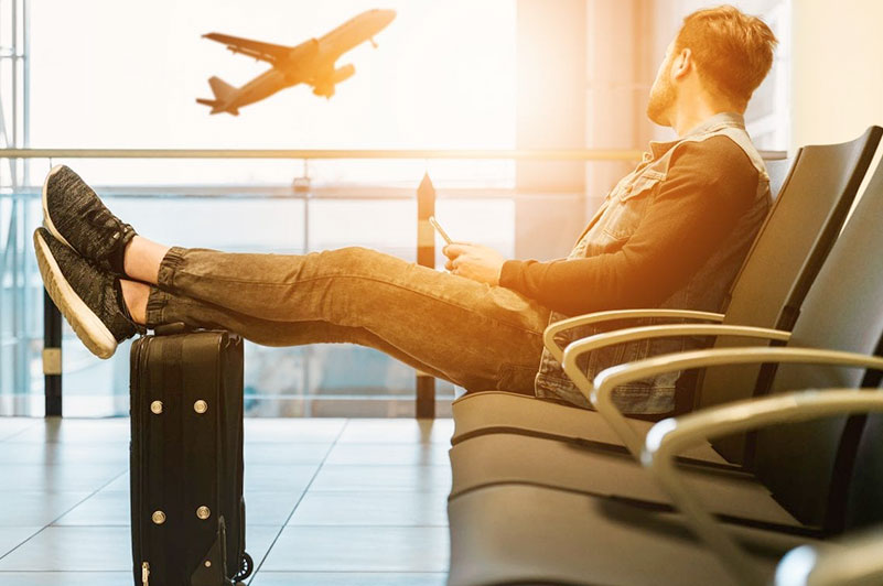 man watching plane flying from gate