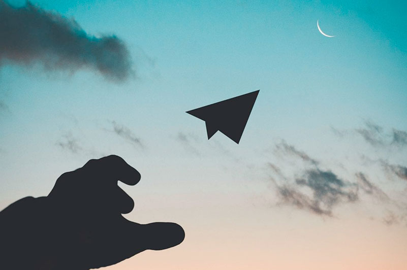 paper plane flying towards the moon